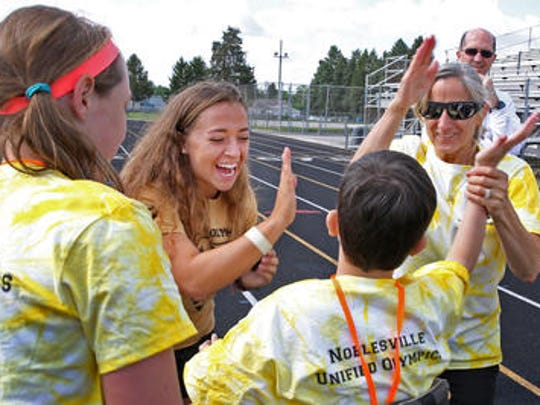 Hannah Potter, center, gives Noah Mezzacapo a high five after his race during the Noblesville schools' Unified Special Olympics event at Hare Chevrolet Field