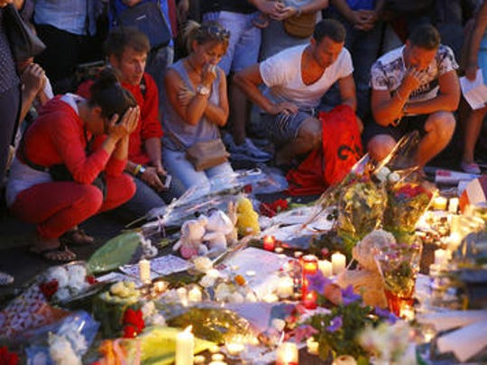 People pay homage to the victims of a truck attack at a makeshift memorial near the area where a truck mowed through revelers in Nice, southern France, Friday, July 15, 2016. A large truck mowed through revelers gathered for Bastille Day fireworks in Nice, killing more than 80 people and sending people fleeing into the sea as it bore down for more than a mile along the Riviera city's famed waterfront promenade. (AP Photo/Francois Mori)