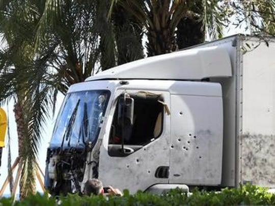 A picture taken on July 15, 2016 shows the truck, riddled with bullets, that was driven by a man through a crowd celebrating Bastille Day being towed away by breakdown lorry in the French Riviera city of Nice. / AFP PHOTO / BORIS HORVATBORIS HORVAT/AFP/Getty Images