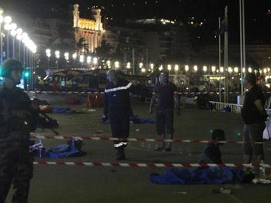 Soldiers, police officers and firefighters walk near dead bodies covered with a blue sheets on the Promenade des Anglais seafront in the French Riviera town of Nice on July 15, 2016, after a van drove into a crowd watching a fireworks display. At least 75 people were killed when a truck drove into a crowd watching a fireworks display in the French resort of Nice, a lawmaker said on July 15. / AFP / VALERY HACHE