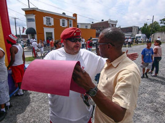 """Wilmington Guardian Angels Chapter Commander Marcos """"The Punisher"""" Velez, Left, hands out a certificate of appreciation during the Project Blue Tape Wilmington event that honors law enforcement in Wilmington."""