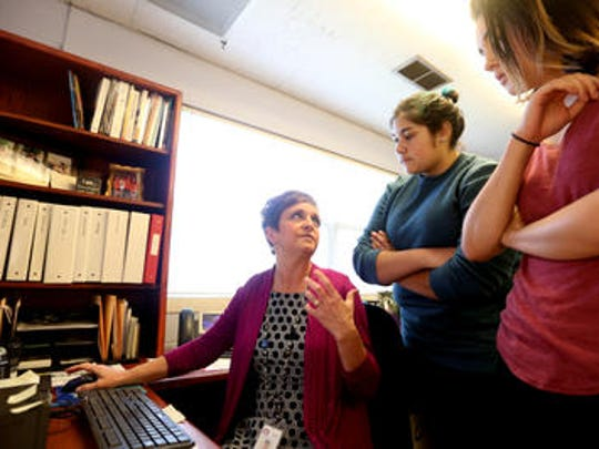Tami Walter, left, talks to Early College High School students Antonia Castro, 18, center, and Victoria Seaton, 18 about plans for next May's high school prom. Walter donates her time to planning proms for two of the city's high schools.