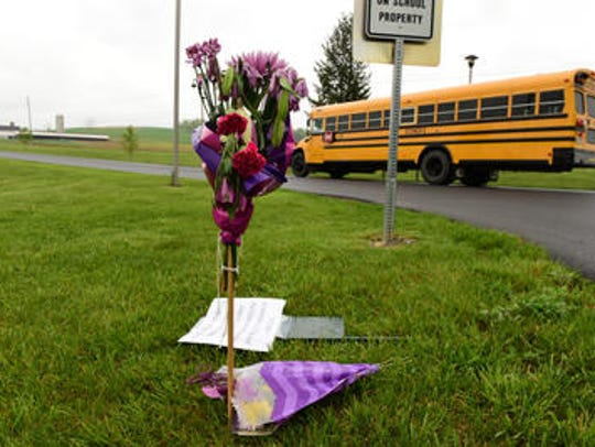 A school bus drives past flowers that were left at