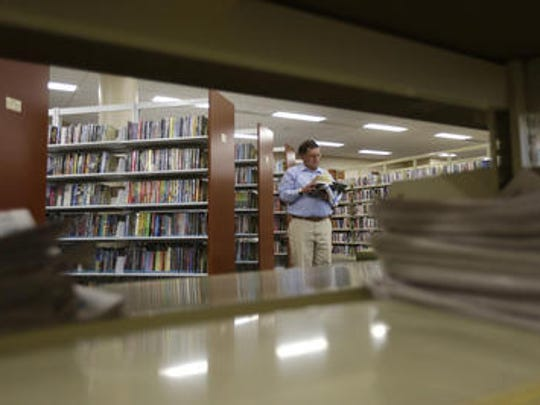 A man peruses a book on the second floor of Everett Roehl Marshfield Public Library.