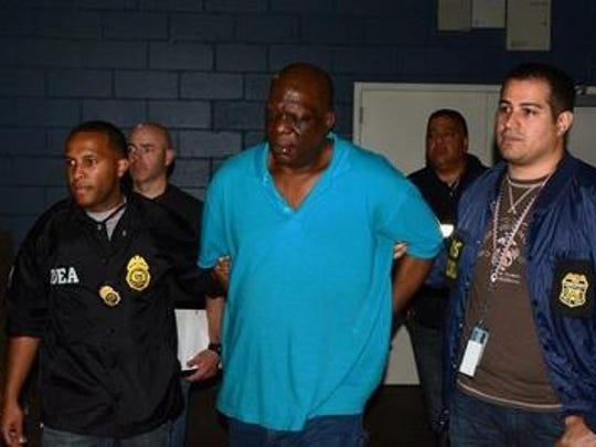 "James ""Pepsi"" Holder is shown in the custody of federal agents in a March 2014 file photo."