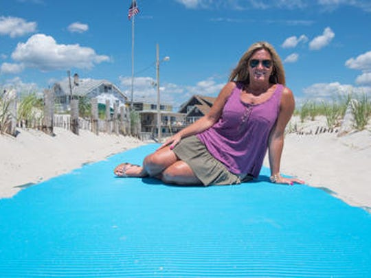 Jessica Krill of Toms River is on a crusade to make beaches more accessible for disabled people. Here, she sits on a beach access mat on a Seaside Park beach. Seaside Park agreed this week to use Matrax to make a longer beach mat that will allow greater access for disabled beachgoers.