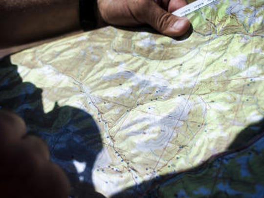 Lewis and Clark Deputy Greg Holmund holds a map marking residences near the Lookout Fire with black dots Sunday, July 16.