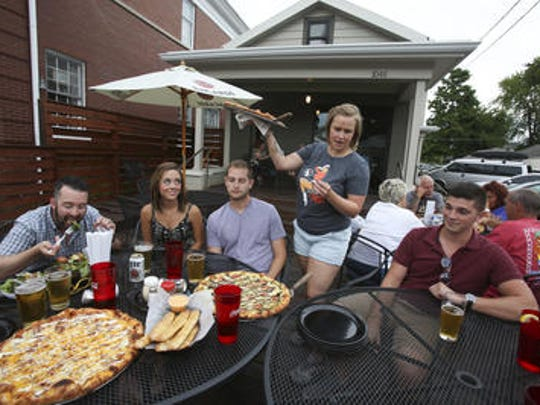 Alaina Nixon, standing, serves pizza to a group at