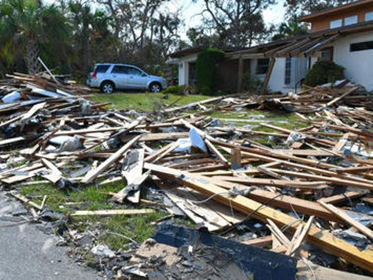 Bill Burton cleared debris off his front yard on Anglers