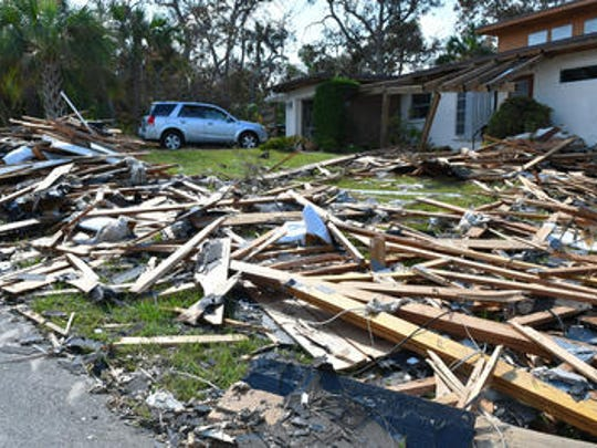Bill Burton cleared debris off his front yard on Anglers Drive in Palm Bay last month, after a home about a 150 yards away lost it's roof and it landed on his property during a tornado spawned by Hurricane Irma.