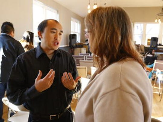 The Rev. Yauo Yang mingles with one of his congregaton