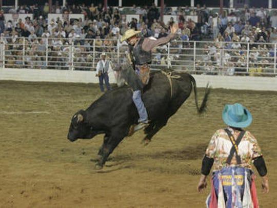 A clown watches a cowboy ride a bull at the Cowtown