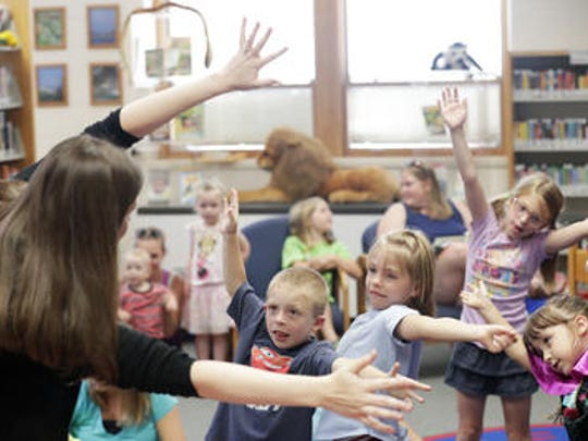 Children dance to a song led by children's librarian Karin Adams during story time at the Brown County Library's Denmark branch on Tuesday, July 24, 2018 in Denmark, Wis.