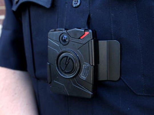 A body camera is clipped to a police officer's uniform.