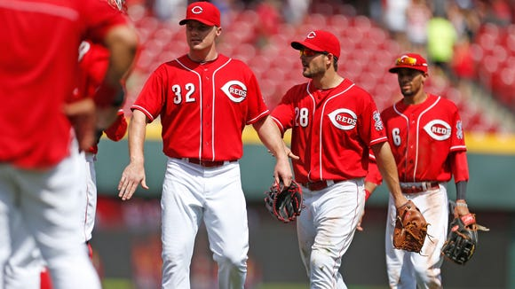 The Reds' Jay Bruce (32), Chris Heisey (28) and Billy Hamilton (6) celebrate the team's 4-2 win over the Chicago Cubs in Game 1 of Tuesday's doubleheader at Great American Ball Park.