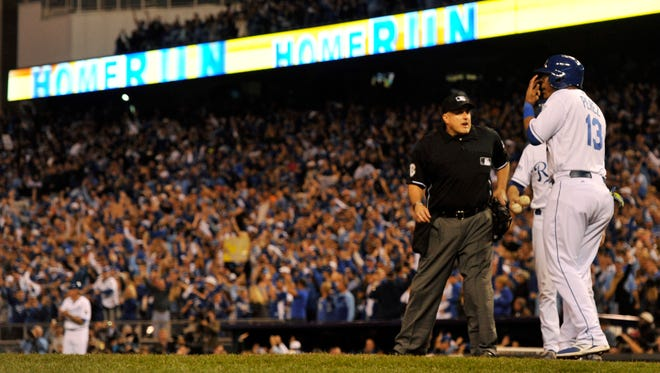 Kansas City Royals catcher Salvador Perez (13) is held back by umpire Eric Cooper (56) as he yells towards San Francisco Giants relief pitcher Hunter Strickland (not pictured) in the sixth inning during game two of the 2014 World Series at Kauffman Stadium.