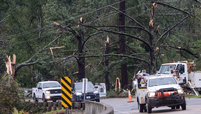 Utility workers drive by damaged trees along Robinson Bridge Road in Liberty early Monday.