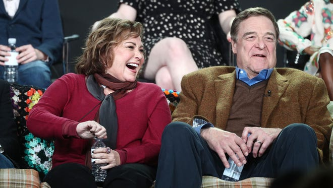 Roseanne Barr, left, and John Goodman, sitting on a replica of the famed 'Roseanne' couch, take part in a panel about the sitcom's revival at the winter TV press tour in Pasadena, Calif.