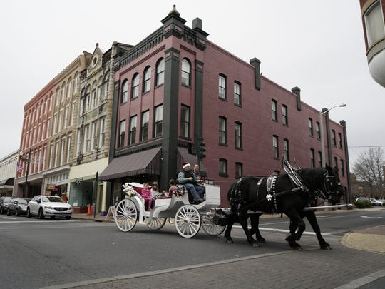 A horse drawn carriage is driven down West Beverley Street during the Small Business Saturday event in downtown Staunton on Saturday, Nov. 28, 2015.