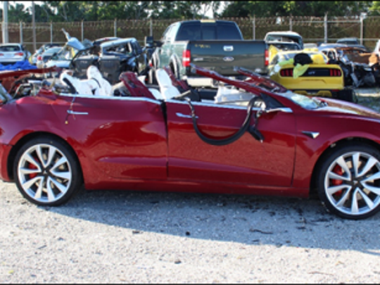 Tesla Model 3 with extensive roof damage photographed postcrash at tow yard.