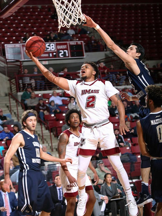 Massachusetts' Luwane Pipkins shoots past George Washington's Yuta Watanba, top right, during the first half of an NCAA college basketball game Wednesday, Feb. 14, 2018, in Amherst, Mass. (J. Anthony Roberts/The Republican via AP)