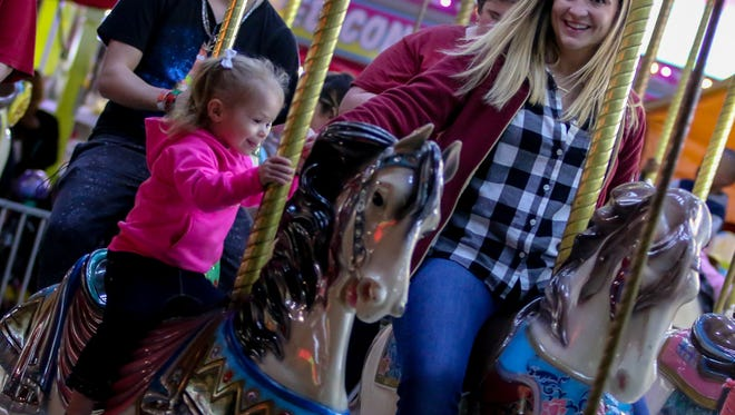 People ride the merry-go-round during the 83rd annual Pensacola Interstate Fair on Tuesday, October 24, 2017. The fair runs through Sunday, Oct. 29.