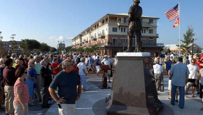 Scores of people check out the life-size bronze statue of Spanish explorer Don Tristan de Luna after its unveiling Thursday at Plaza de Luna to celebrate the 450th anniversary of the founding of Pensacola.  People take a photos of a life-size bronze Spanish conquistador after it's unveiling on Thursday at Plaza de Luna to celebrate the 450th anniversary of the founding of Pensacola.