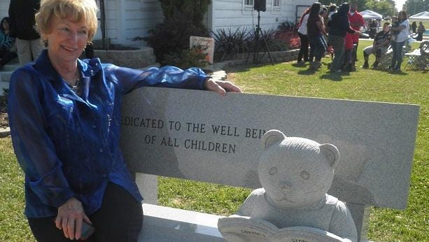 "Billie Shawl sits on the ""Community for Child Well Being"" bench in Farmersville"