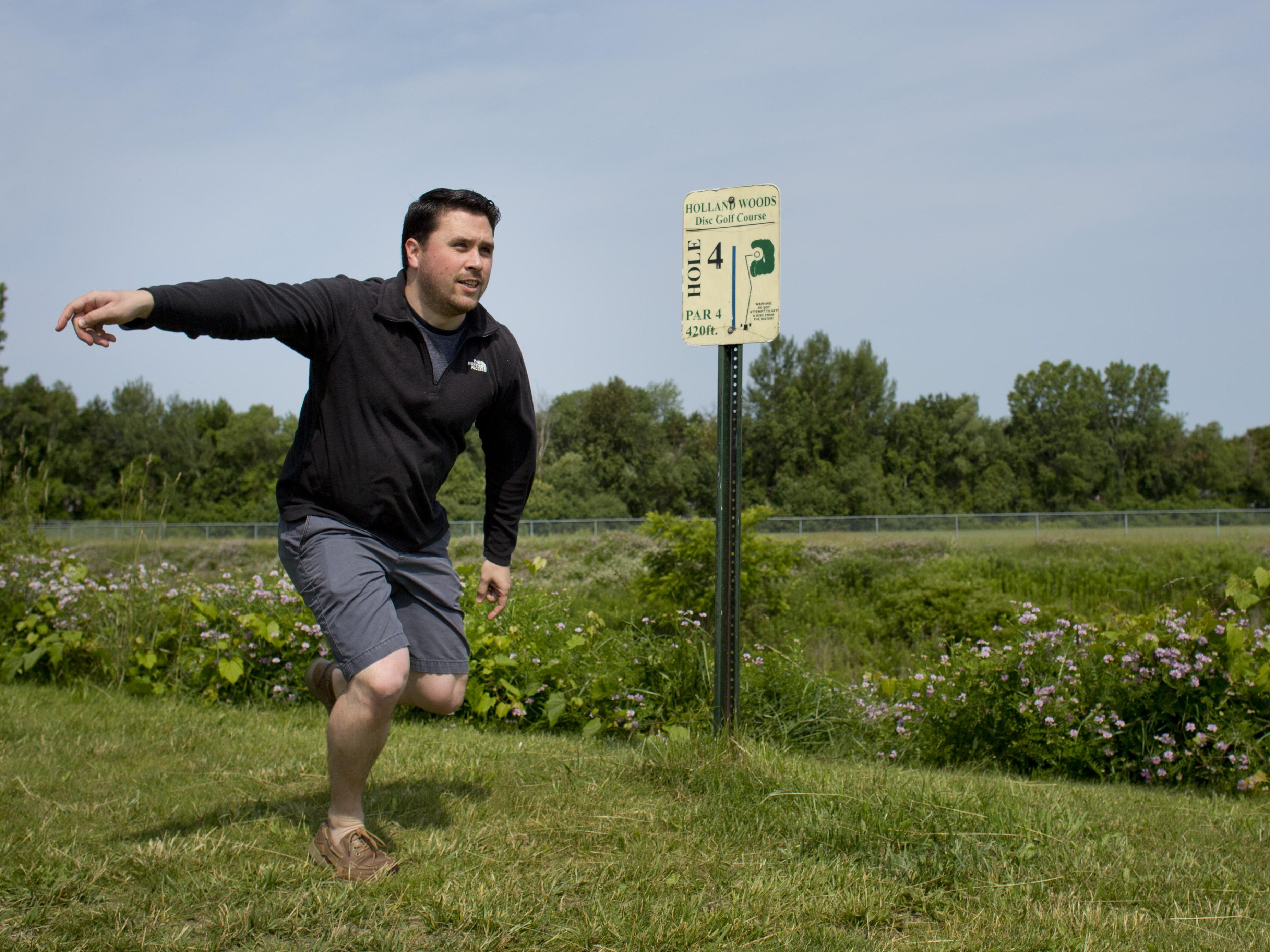Paul Costanzo watches his disc while playing disc golf Friday, July 3, 2015 at Holland Woods in Port Huron.