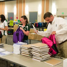 Colorado State University President Tony Frank talks with other School is Cool volunteers as they fill backpacks with school supplies for Poudre School District students, August 6, 2014.