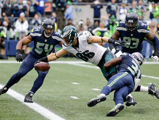 Philadelphia Eagles tight end Zach Ertz (86) gets the ball across the line for a touchdown as he is tackled by Seattle Seahawks strong safety Kam Chancellor, lower right, middle linebacker Bobby Wagner (54) and defensive tackle Tony McDaniel (93) in the first half of an NFL football game, Sunday, Nov. 20, 2016, in Seattle. (AP Photo/Stephen Brashear)