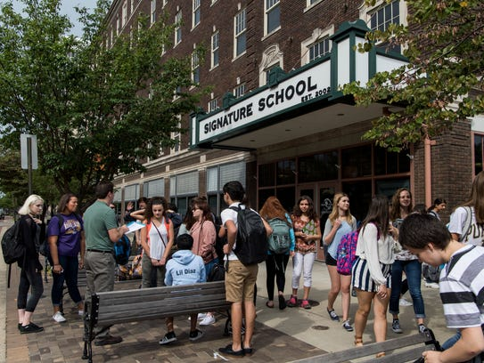 Students stand outside of the Signature School's main