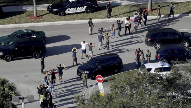 In this Feb. 14, 2018 file photo, students hold their hands in the air as they are evacuated by police from Marjory Stoneman Douglas High School in Parkland, Fla., after a shooter opened fire on the campus.