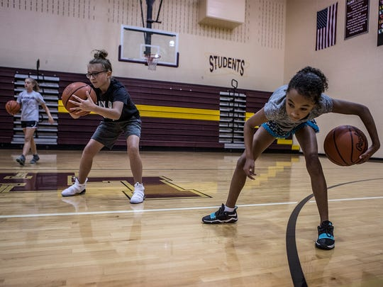 Cali Beard and Darianna Barnes works on skills drill during a summer basketball camp at Licking Heights High School.