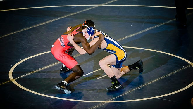 Jack Snauko ,right, of Grand Ledge comes to grips with Abdelbassit Adam of Everett during their 130 lbs. District finals match Wednesday February 8, 2017 in East Lansing.  KEVIN W. FOWLER PHOTO
