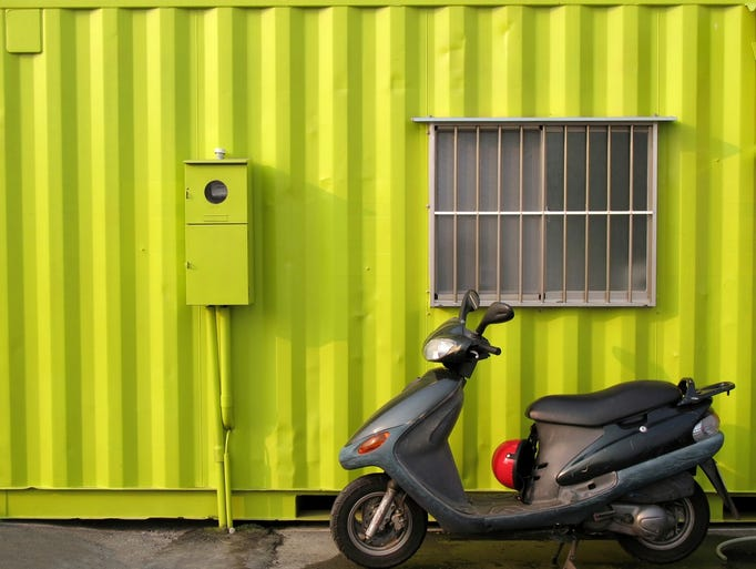 A shipping container used as a house with a scooter