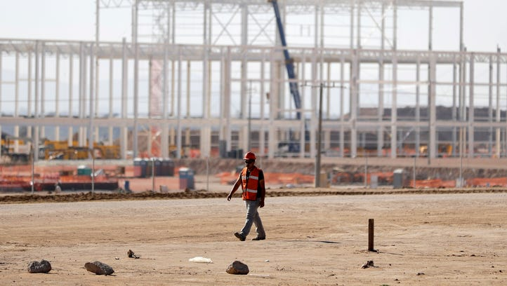 A man walks past the nearly deserted construction site