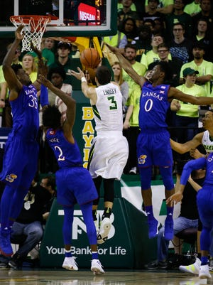Baylor Bears guard Jake Lindsey (3) is defended by Kansas Jayhawks guard Marcus Garrett (0) as he drives the lane during the first half at Ferrell Center.