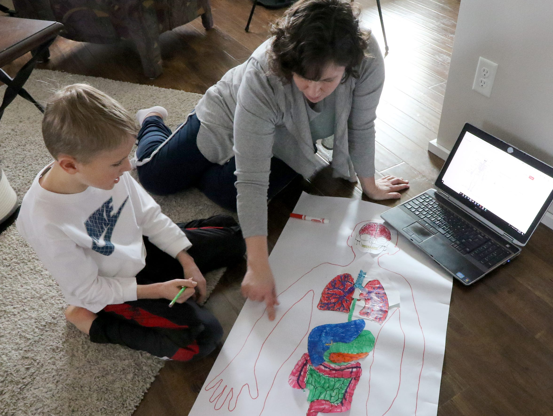 Colleen Boehm works with her son, Nick, 9, to identify major bones and joints on a full-size tracing of Nick for a unit on human anatomy.