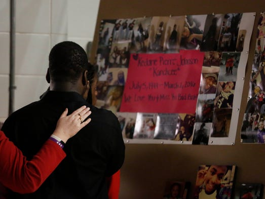 Visitors look over a collage of photos featuring 16-year-old
