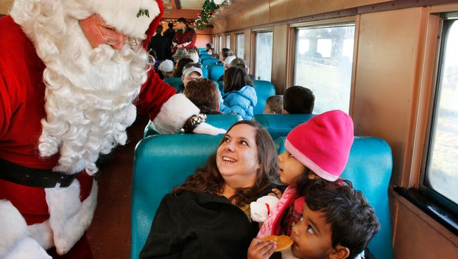 Oliver, right, and Amelia Gollapudi, 2 and 4, respectively, and their mother Sylvia are greeted aboard the Polar Bear Express on their train ride from the Fishers Train Station to Noblesville and back during the Indiana Transportation Museum's 17th annual event on Saturday, Dec. 10, 2011.