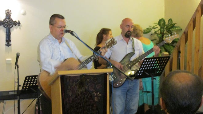 The Rev. Andrew Brunson, left, plays the guitar during a service at Resurrection Church in Izmir, Turkey, in 2014.