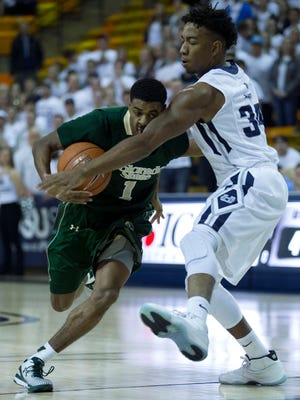 CSU guard Antwan Scott tries to drive against Utah State's Chris Smith during Wednesday night's game in Logan, Utah. The Aggies won 72-55, sending CSU to its fourth loss in the past six games.