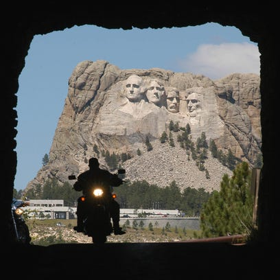 A biker rolls through a tunnel with Mount Rushmore
