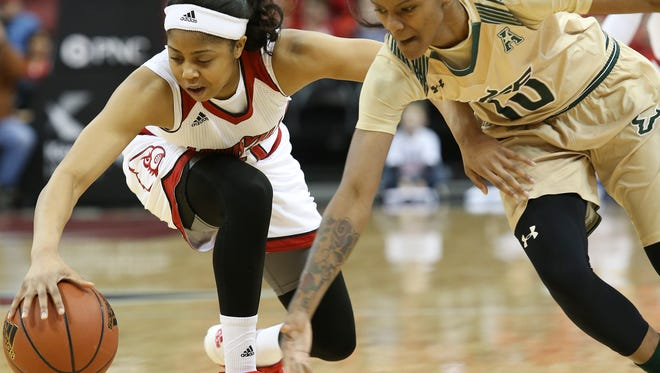 U of L's Arica Carter, #11, tries to maintain control of the ball against USF's Courtney Williams, #10, during their game at the KFC Yum! Center.Feb. 15, 2016