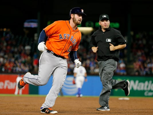 Houston Astros' Tyler White rounds third as base umpire Clint Fagan, right, watches White trot home following his solo home run that came off a pitch from Texas Rangers starting pitcher Cole Hamels in the sixth inning of a baseball game, Wednesday, April 20, 2016, in Arlington, Texas. (AP Photo/Tony Gutierrez)