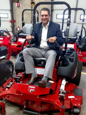 Briggs & Stratton Corp. CEO Todd Teske inspects a new Ferris commercial lawn mower at the company's headquarters in Wauwatosa. Briggs and Teske are bringing manufacturing production jobs back to the United States.