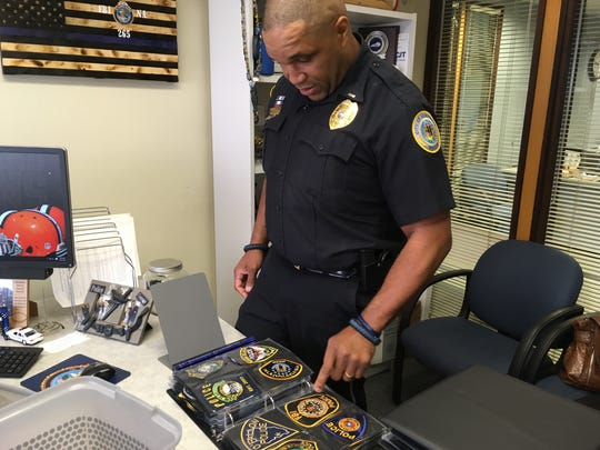 Lt. Poynter shows police patches he collected from classmates at the FBI National Academy