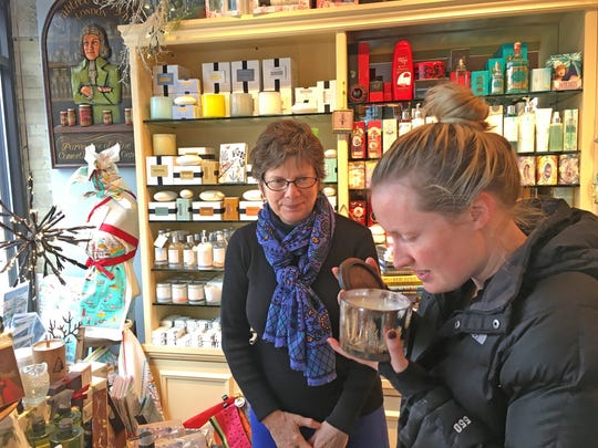 Laura Dewire of Cincinnati, Ohio, smells a Fraser fir candle as Soaps & Scents owner Karen Tibbitts looks on in this file photo. Soap & Scents, 7600 Harwood Ave., Wauwatosa, is closing after 35 years in business.