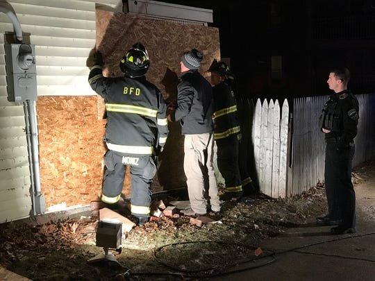 Burlington firefighters and other personnel help install plywood over a hole left after a car hit a house Monday evening, Dec. 26, 2016, in the city's Old North End.